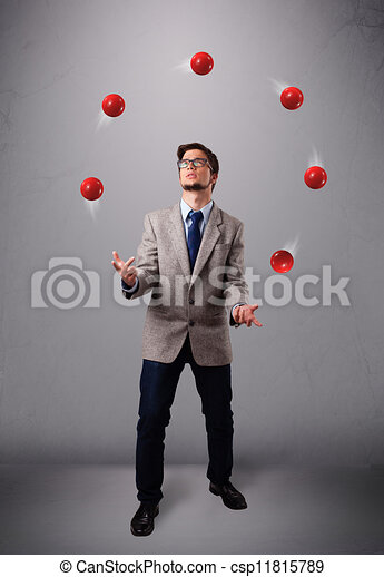 young man standing and juggling with red balls - csp11815789