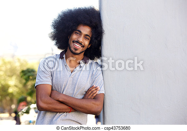 young man standing with arms crossed leaning on white wall - csp43753680