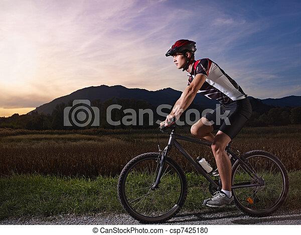 young man training on mountain bike at sunset - csp7425180