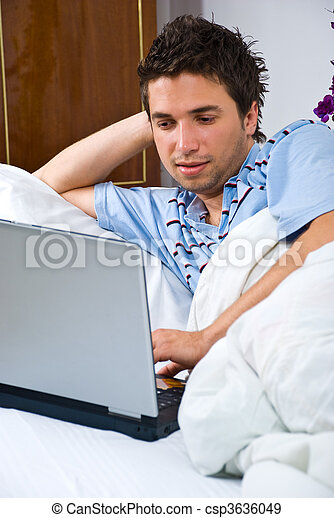 Young man using laptop in bed - csp3636049