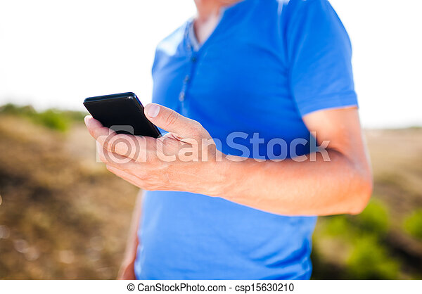 Young man using mobile smart phone, summer outdoor  - csp15630210