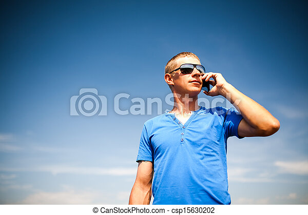 Young man using mobile smart phone, summer outdoor  - csp15630202