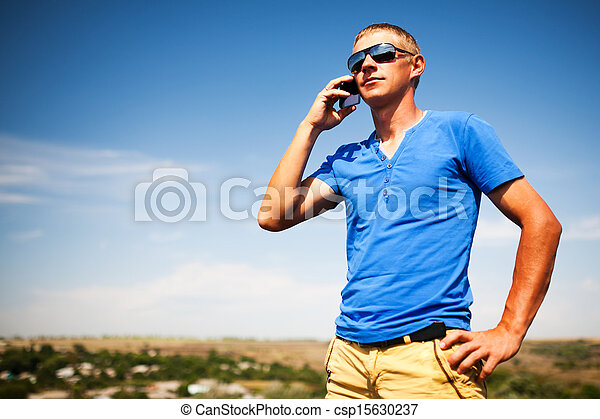 Young man using mobile smart phone, summer outdoor  - csp15630237