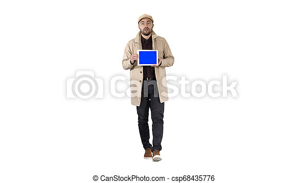 Young man walking, talking and showing digital tablet with blue screen mockup on white background. - csp68435776