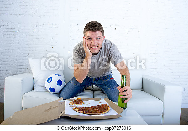 young man watching football game on television nervous and excited suffering stress on sofa couch - csp37275016
