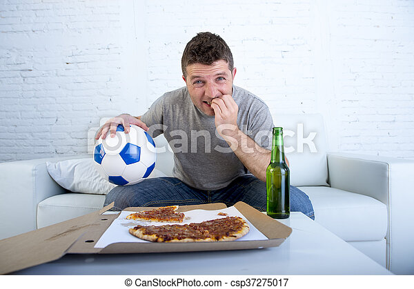 young man watching football game on television nervous and excited suffering stress biting fingernail on sofa - csp37275017
