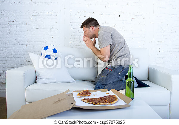 young man watching football game on television nervous and excited suffering stress praying god for goal - csp37275025