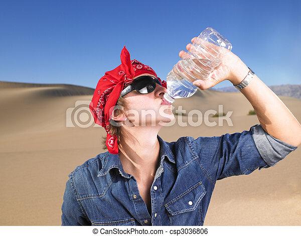 Young Man Wearing Sunglasses and Bandana Drinking Water - csp3036806