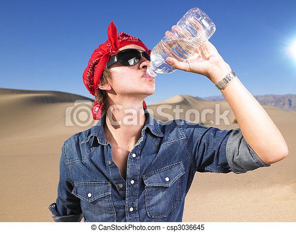 Young Man Wearing Sunglasses and Bandana Drinking Water - csp3036645