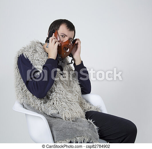 young man with a mask on his face sits in a white chair - csp82784902