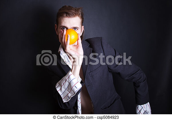 young man with an orange in his hand - csp5084923