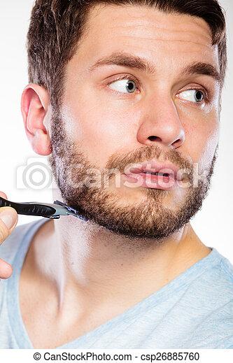 Young man with beard holding razor blade - csp26885760