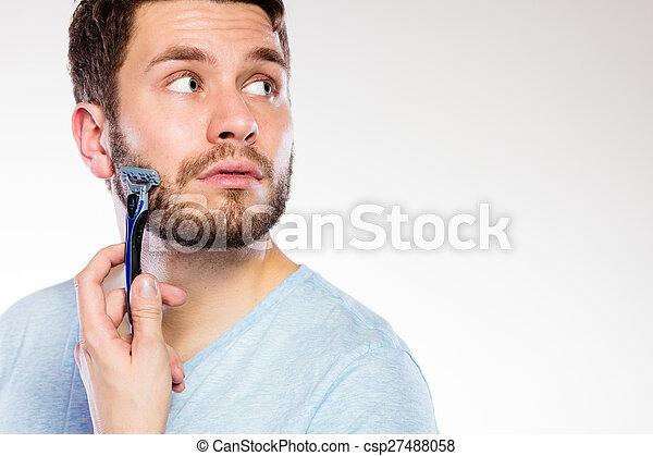 Young man with beard holding razor blade - csp27488058