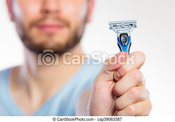 Young man with beard showing razor blade - csp39063387