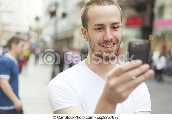 Young Man with cell phone walking - csp9257877