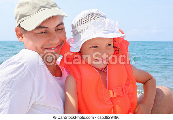 young man with little girl in orange lifejacket on beach - csp3929496