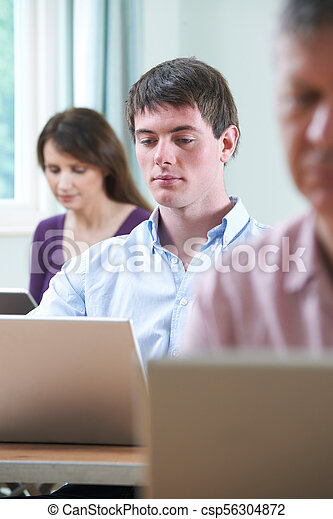 Young Man Working On Laptop In Adult Education Class - csp56304872