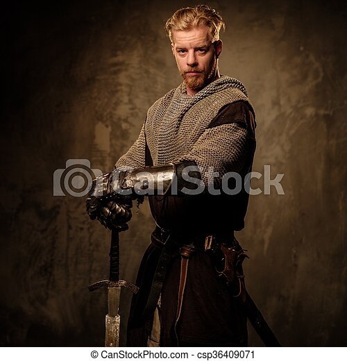 Young medieval knight posing on dark background.  - csp36409071