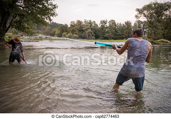 young men having fun with water guns - csp62774463