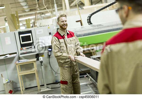Young men working in furniture factory - csp45936011