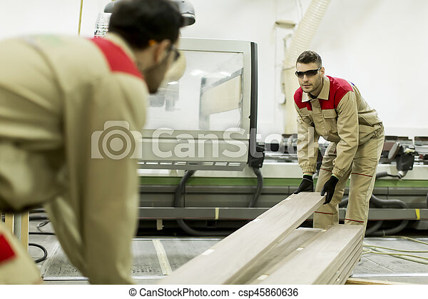 Young men working in furniture factory - csp45860636