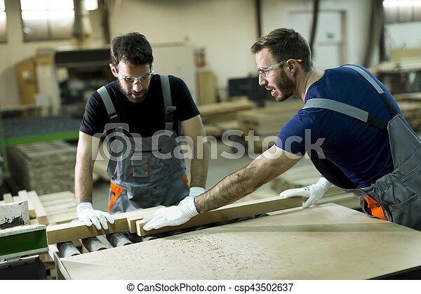 Young men working in lumber workshop - csp43502637