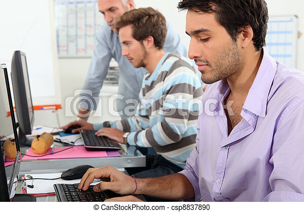Young men working on computers - csp8837890