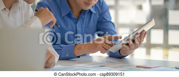 Young men working on tablet together. - csp89309151
