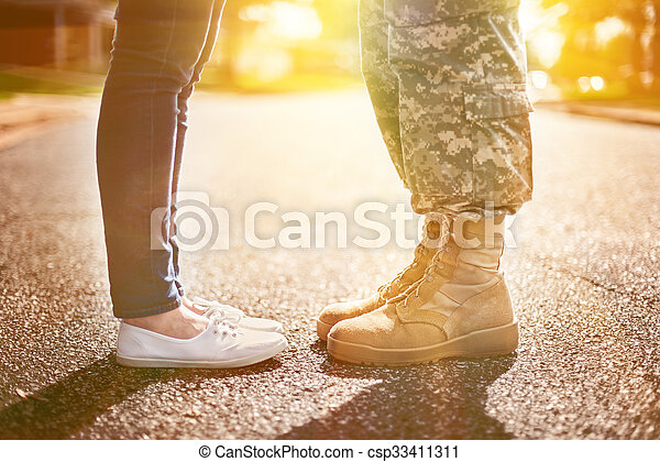 Young military couple kissing each other, homecoming concept, soft focus,warm orange toning applied - csp33411311
