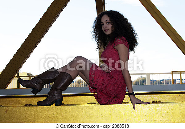 Young Mixed Black Woman Red Dress Sitting - csp12088518