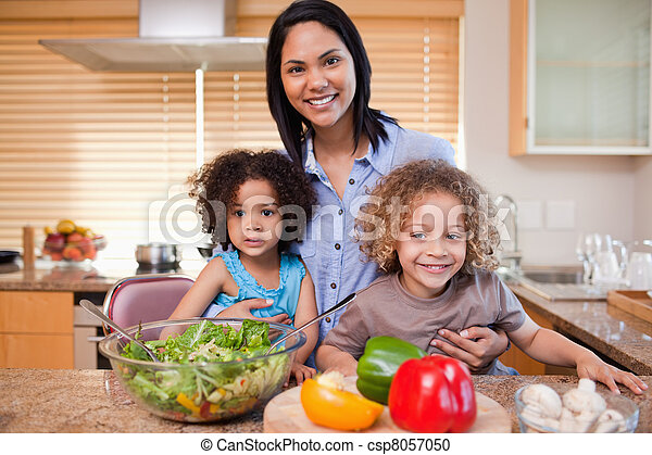 Young mother and her daughters preparing salad in the kitchen together - csp8057050