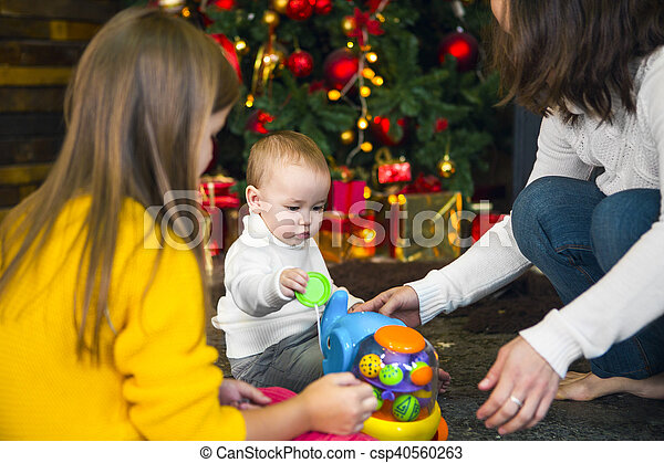 Young mother and her two children opening a christmas presents by a ...