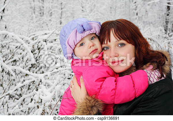 Young mother hugs little daughter in woods in snow at winter - csp9136691