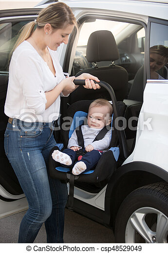 Young Mother Installing Car Child Seat With Baby