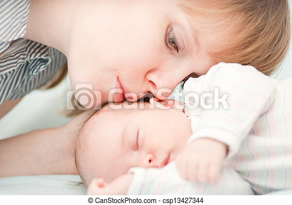 young mother kissing her slipping newborn baby - csp13427344