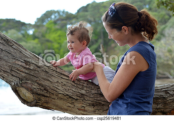 Young mother play outdoor with her baby - csp25619481