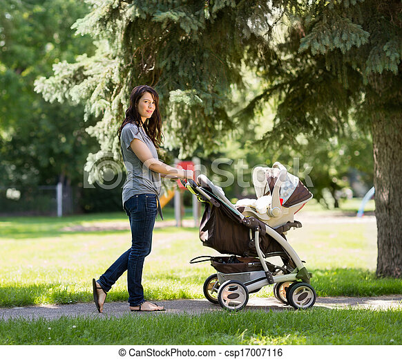 Young Mother Pushing Stroller In Park Full Length