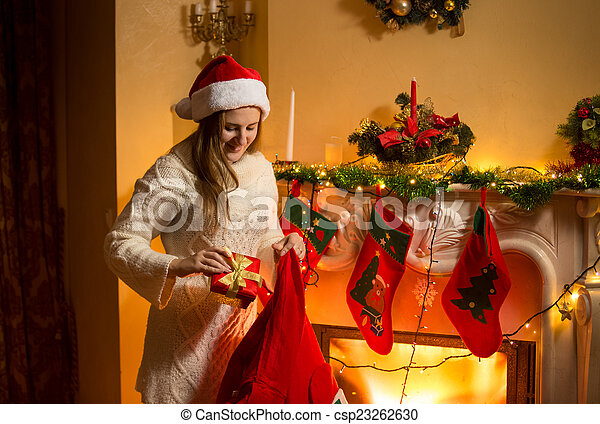 Portrait of young mother putting christmas gifts in stockings ...