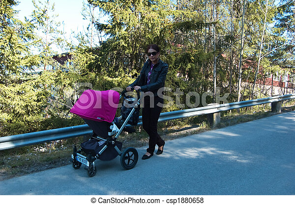 Young mother walking with pram - csp1880658