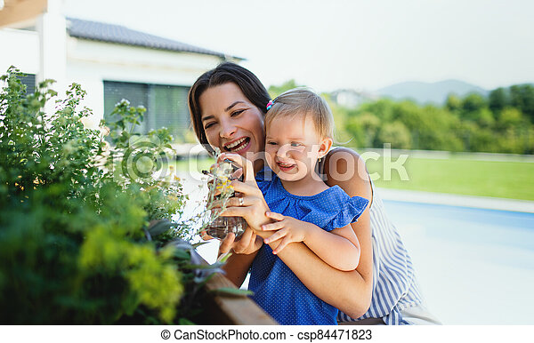 Young mother with small daughter outdoors in backyard garden, spraying plants. - csp84471823