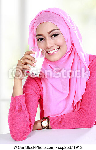 young muslim woman drinking a glass of milk - csp25671912
