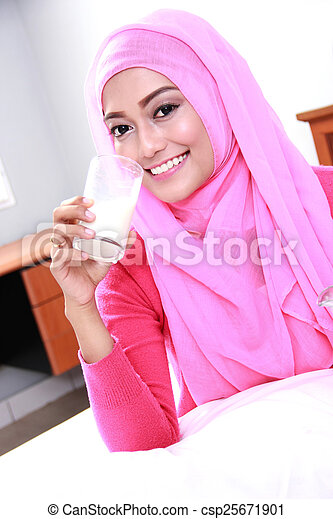 young muslim woman drinking a glass of milk - csp25671901