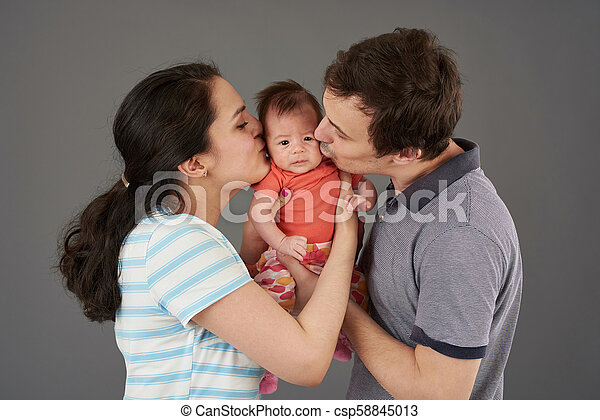 Young parents kiss small baby - csp58845013