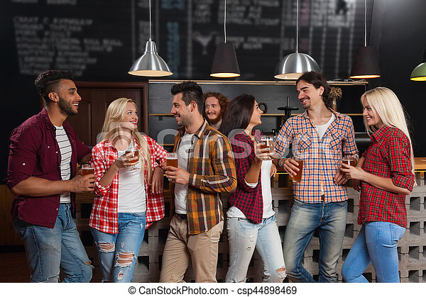 Young People Group In Bar, Happy Smiling Friends Pub, Drink Beer Talking - csp44898469