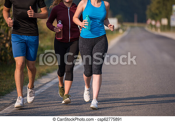 young people jogging on country road - csp62775891