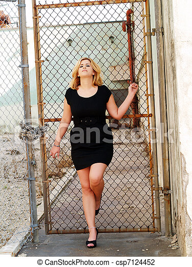 Young plump caucasian woman black dress cyclone fence - csp7124452