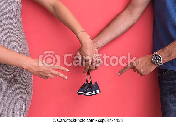 young pregnant couple holding newborn baby shoes - csp62774438