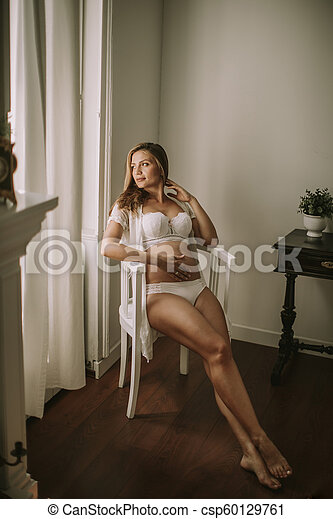 Young pregnant woman sitting in the chair - csp60129761