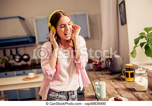 Young pretty girl having fun listening to music in headphones. Female at home in the kitchen drinking tea singing and listening music.