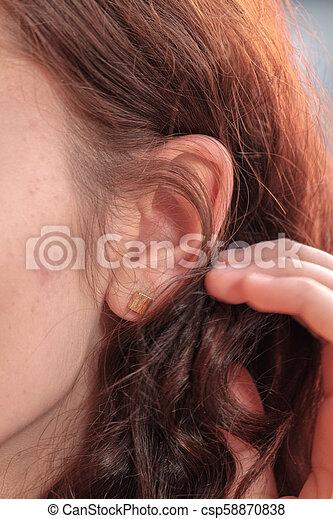 Young pretty redhair woman ear closeup - csp58870838